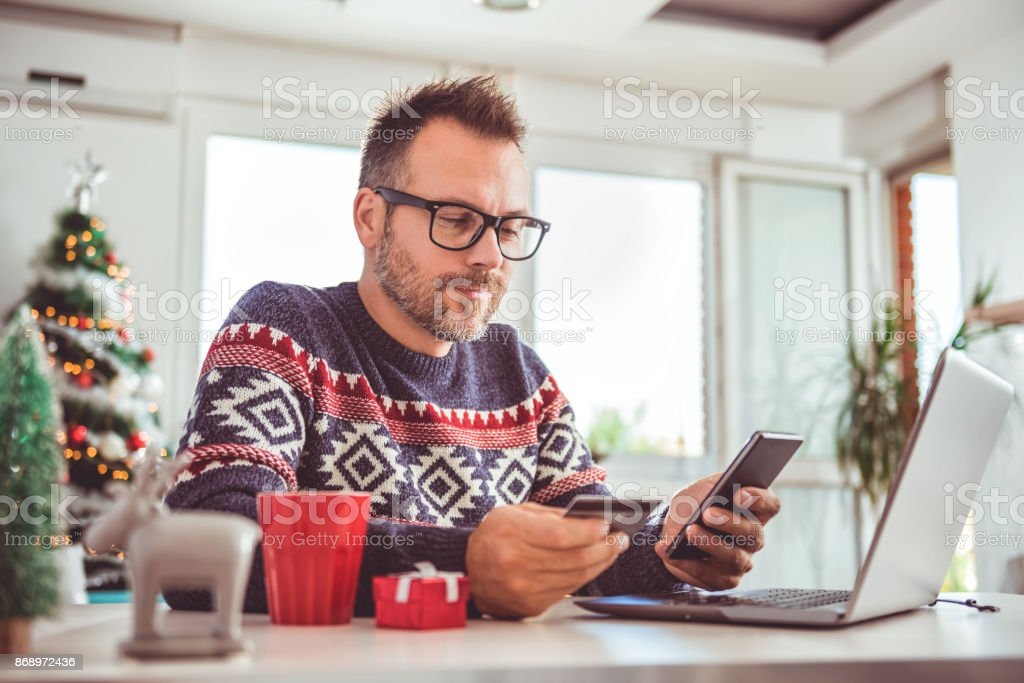 Men holding credit card and using laptop at home office stock photo
