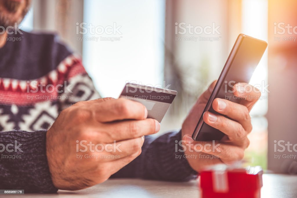 Men wearing blue sweater and eyeglasses holding credit card and using...