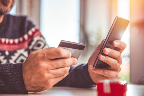 men holding credit card and using smart phone at home office - spending money stock pictures, royalty-free photos & images