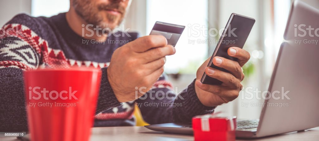 Men holding credit card and using smart phone at home office stock photo