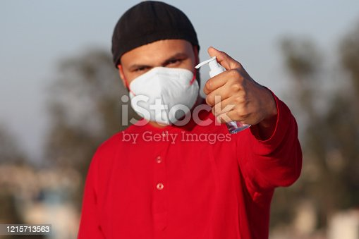 Young men of Indian ethnicity holding hand sanitizer in hand and wearing pollution mask against Coronavirus. Promoting people use hand Sanitizer to protect themselves from virus infection in Corona Virus crisis.