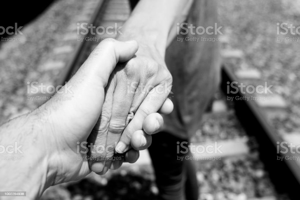 men holding hands on the railroad tracks stock photo