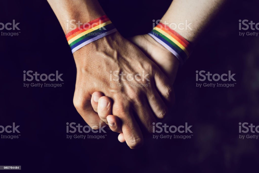 men holding hands with rainbow-patterned wristband stock photo