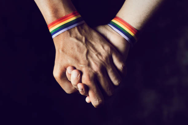 men holding hands with rainbow-patterned wristband closeup of two caucasian men holding hands with a rainbow-patterned wristban on their wrists gay person stock pictures, royalty-free photos & images