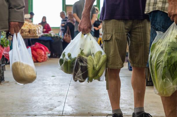 남자는 전형적인 터키 greengrocery 바 자에 야채와 함께 플라스틱 쇼핑 가방을 들고 - 바자 뉴스 사진 이미지