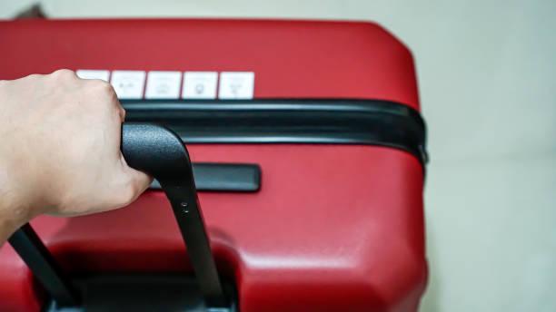männer halten red big suitcase stock foto - trolley kaufen stock-fotos und bilder
