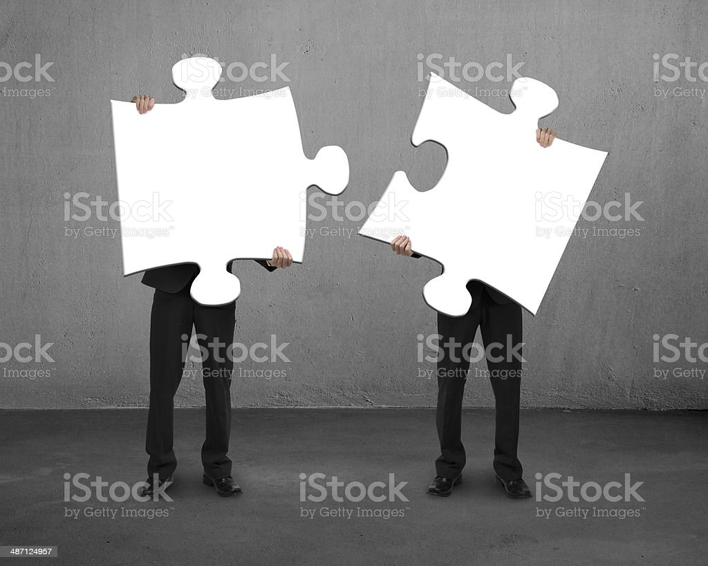 Men holding two puzzles stock photo