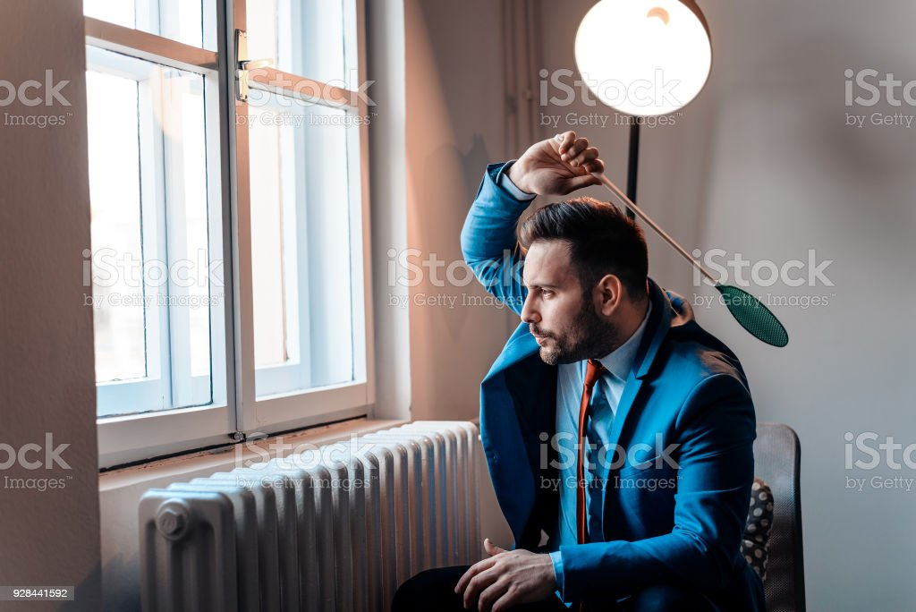Men in a suit hitting a fly with a fly swatter. stock photo