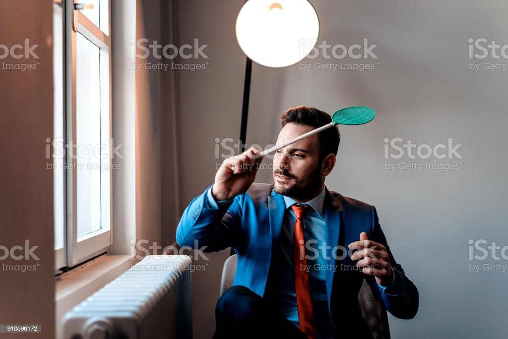 Men in a suit holding a fly swatter sitting near the window. stock photo