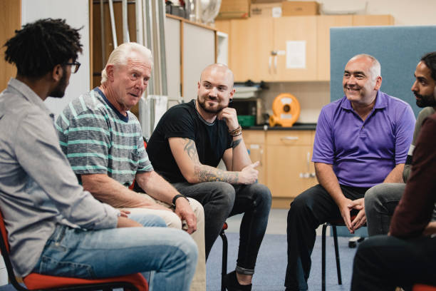 Men in a Support Group Diverse group of men are talking and laughing together in a mental health support group. men stock pictures, royalty-free photos & images