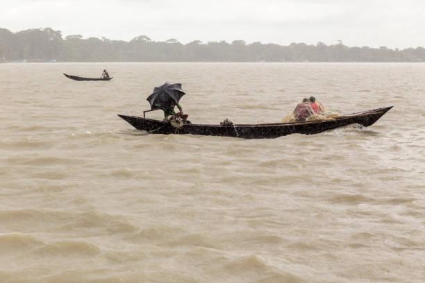 Barisal, Bangladesch - 12. Juli 2016: Männer in einem hölzernen Kanu schützt vor dem Monsunregen auf einem breiten Fluss. – Foto