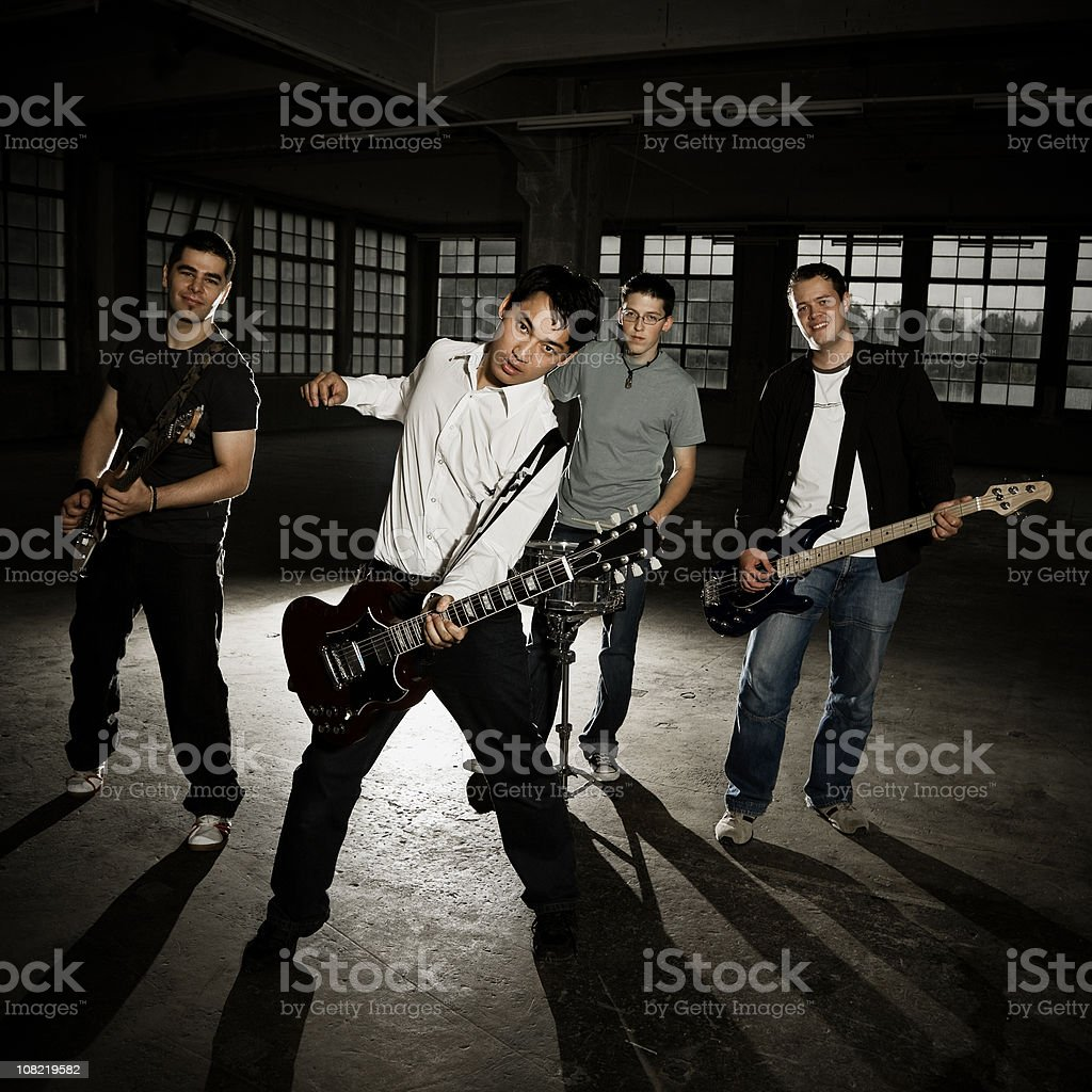 Men in Band Playing Guitar at Empty Factory, Low Key royalty-free stock photo