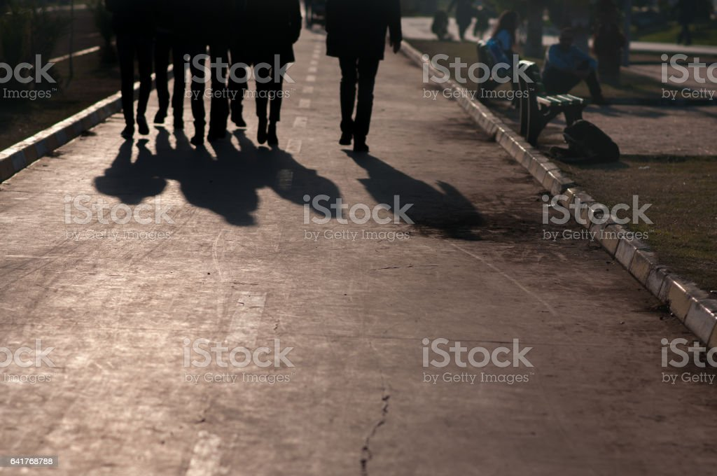 men in black coming along the pavement stock photo