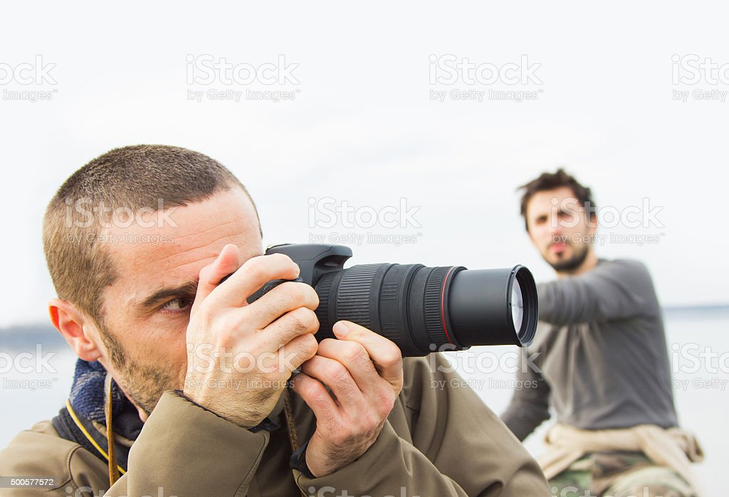 Men in boat on the river, taking photos with camera stock photo
