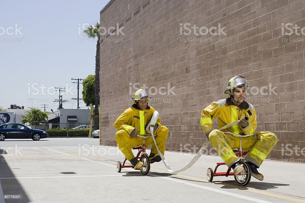 Uomo in abiti su tricycles pompiere foto stock royalty-free