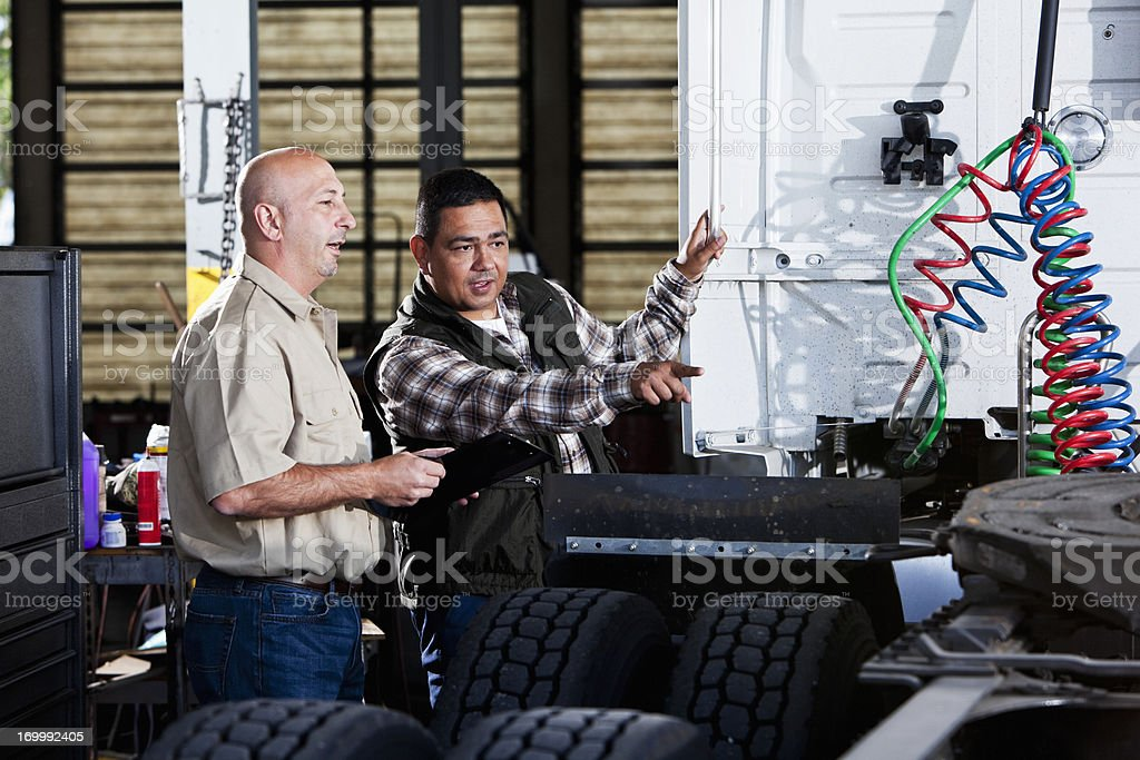 Men in garage with semi-truck royalty-free stock photo