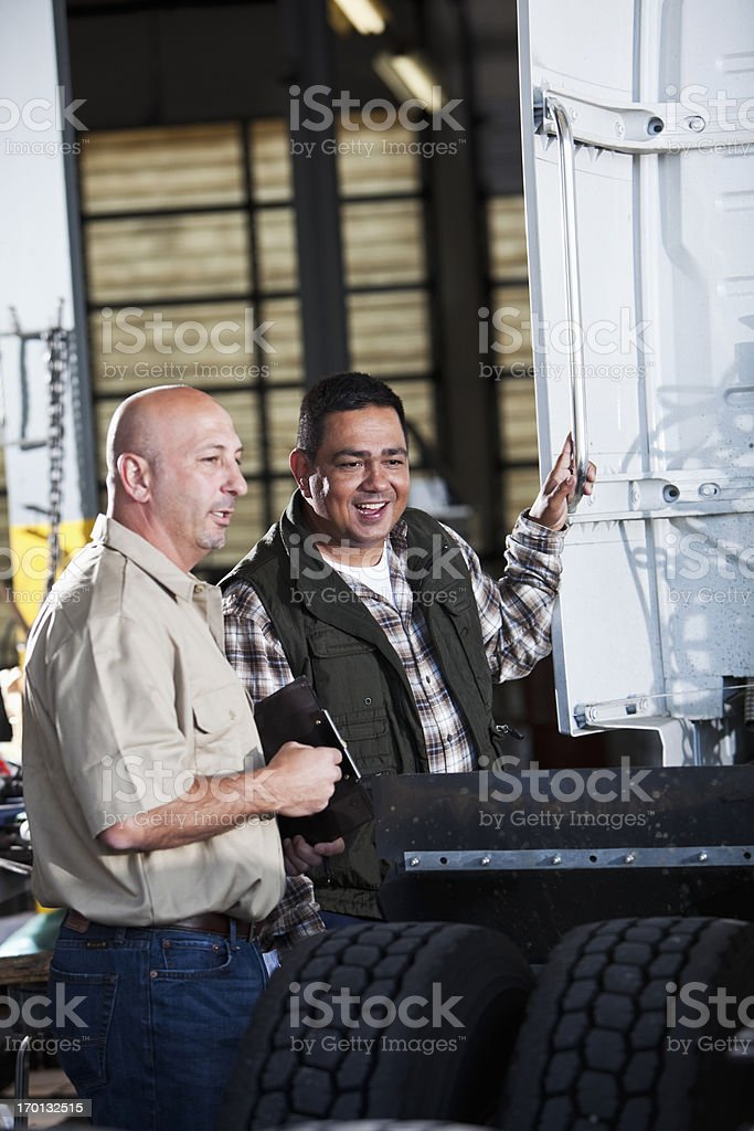 Men in garage with semi-truck stock photo