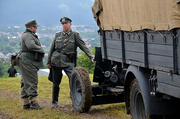Hombres en alemán uniformes durante recreación histórica de 2 ª GUERRA MUNDIAL batalla - foto de stock