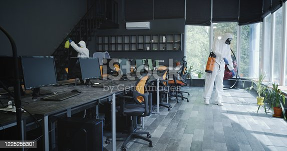 Full shot of men in hazmat suits disinfecting office