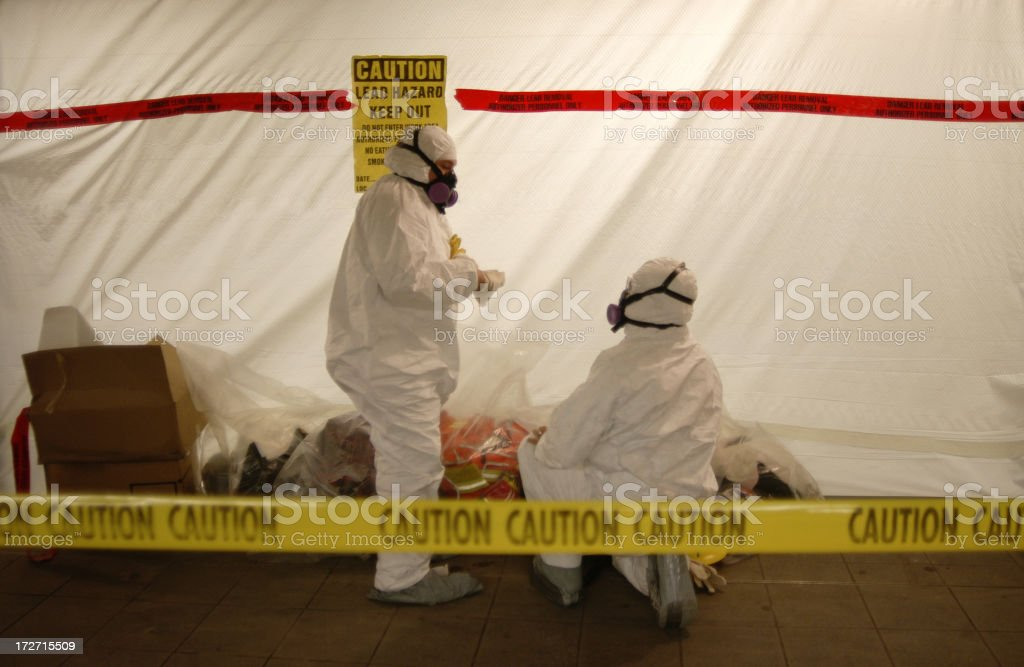 Men in Hazmat suits preparing themselves to work with lead stock photo