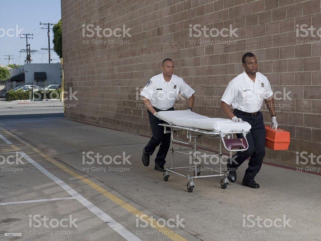 Mężczyźni w Ratownik medyczny stroje naciskając gurney zbiór zdjęć royalty-free
