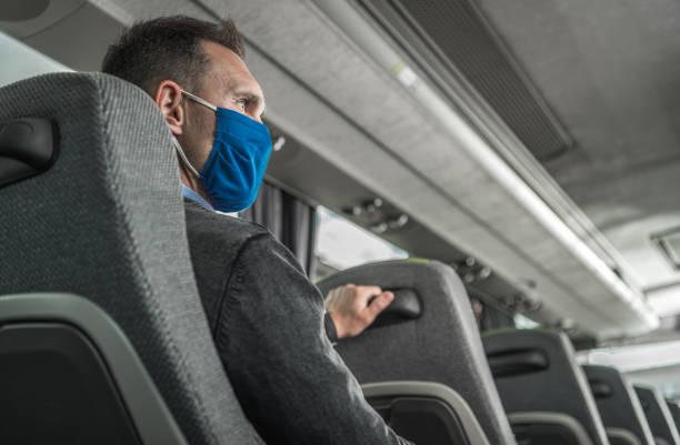 Men in Safety Breathing Mask on His Face Traveling Alone in a Bus Coach stock photo