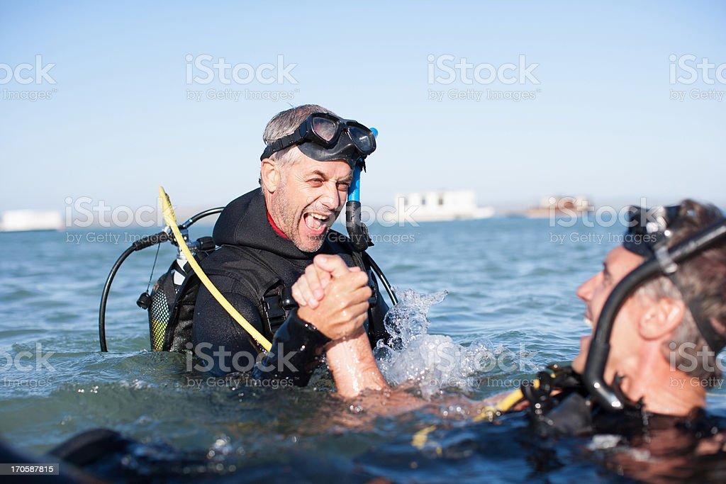 Men in scuba gear holding hands stock photo