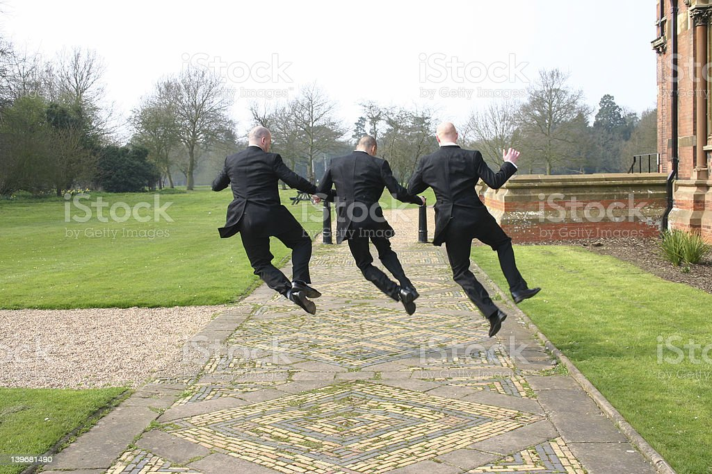 3 men in suits jumping for joy stock photo