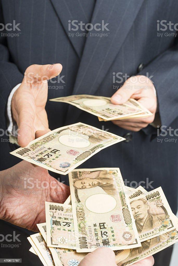 men in suits passing lots of yen cash stock photo