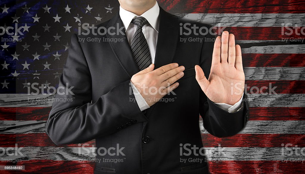 Men in suits taking oath in front of the American flag stock photo