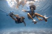 Men skateboarding underwater in the swimming pool