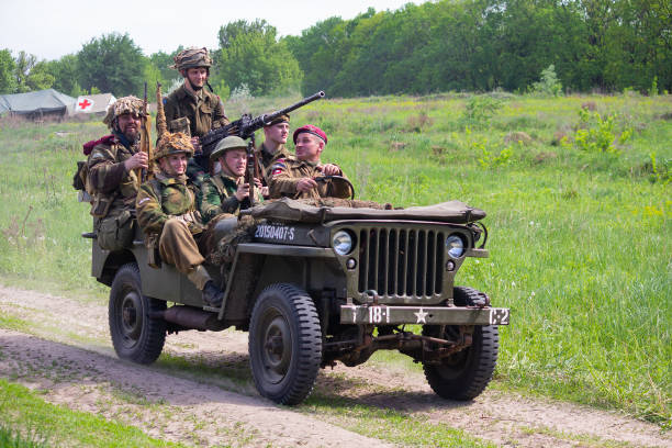 Men in the uniform of American and British soldiers on a jeep during historical reconstruction in honor of the anniversary of victory in the Second World War Kiev, Ukraine - May 09, 2018: Men in the uniform of American and British soldiers on a jeep during historical reconstruction in honor of the anniversary of victory in the Second World War willys stock pictures, royalty-free photos & images