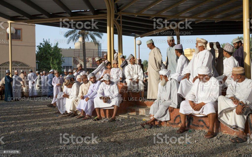 men in traditional clothing gathering at Nizwa goat merket stock photo