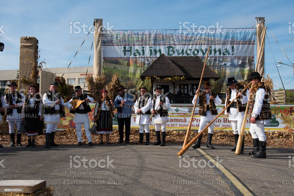Men in traditional costume playing on alpine horns stock photo