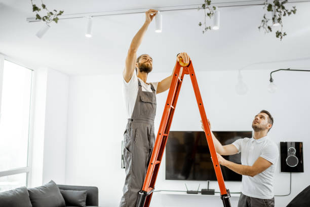 Men installing lights at home stock photo
