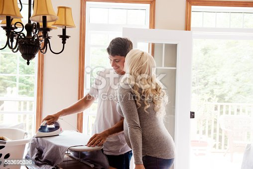 802472024istockphoto Men irons while his pregnant wife gives him a kiss 583695396