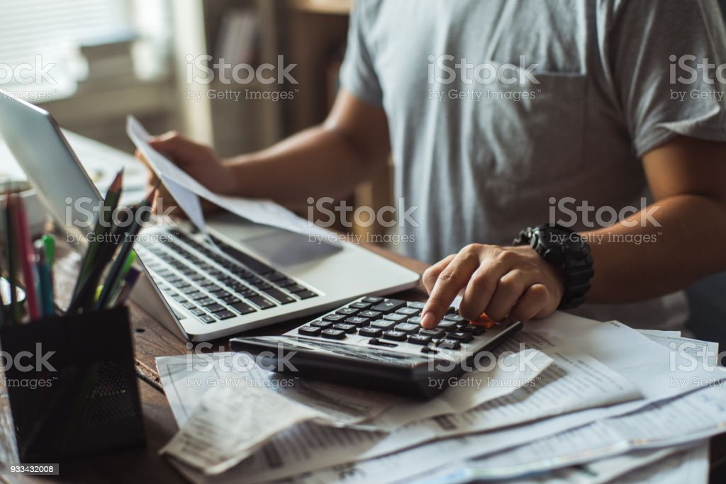 Men is calculating the cost of the bill. She is pressing the calculator. - Foto stock royalty-free di Ambientazione interna