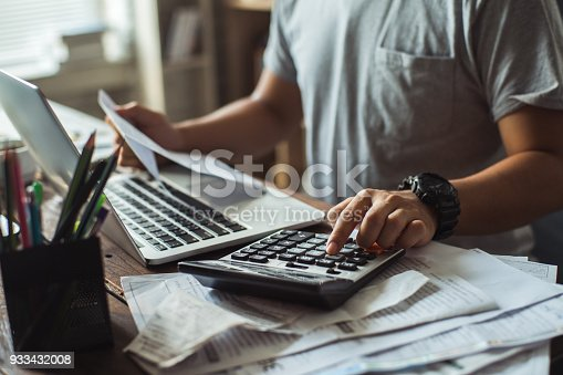 istock Men is calculating the cost of the bill. She is pressing the calculator. 933432008