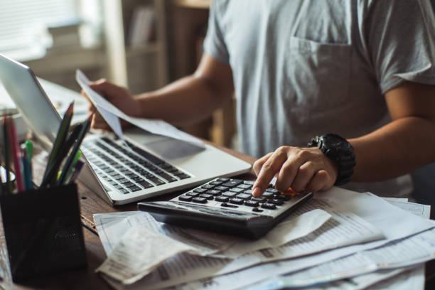 hombres es calcular el costo de la factura. ella está presionando la calculadora. - electronic invoice fotografías e imágenes de stock