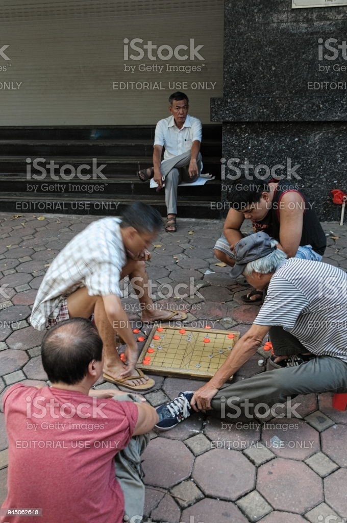 Men is playing Chinese chess on street in Hanoi stock photo