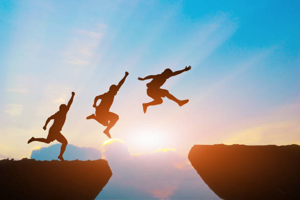 Men jump cliff sun light over silhouette stock photo