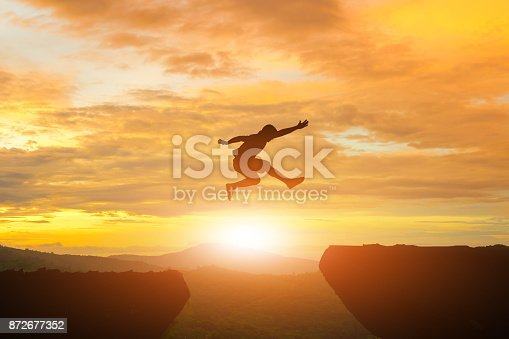 Men jump cliff sun light over silhouette
