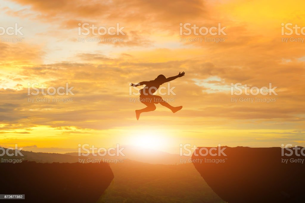 Men jump cliff sun light over silhouette - foto stock