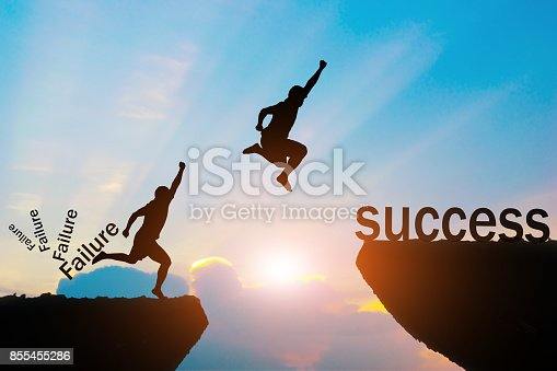 istock Men jump over failure Committed to success. 855455286