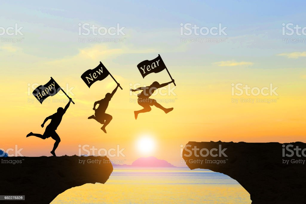 Men jump over silhouette Happy New Year stock photo