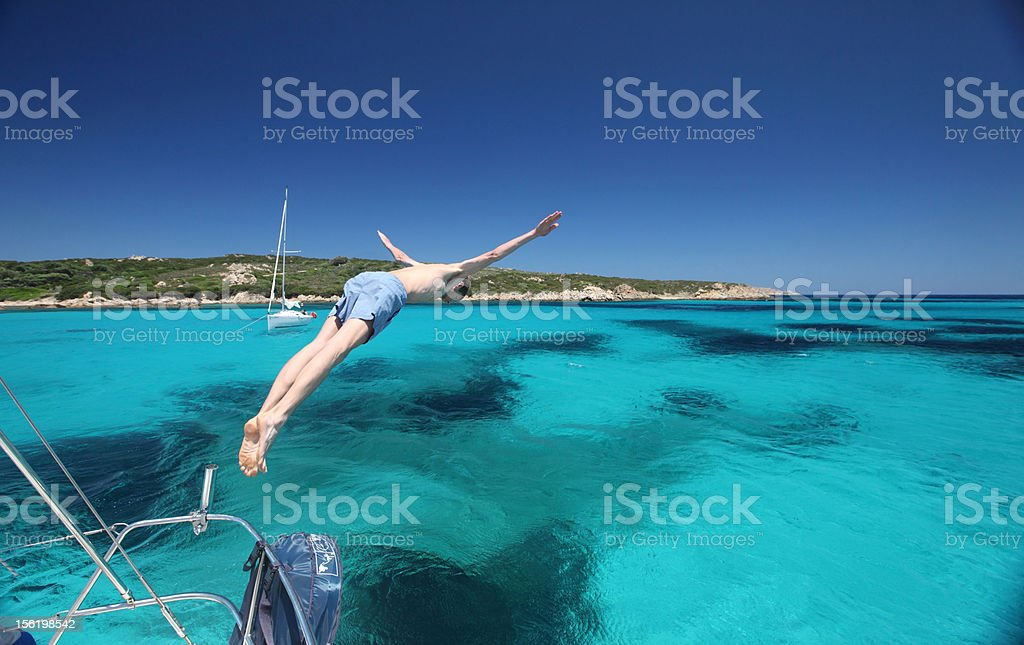 Men jumping off a yacht in Sardinia royalty-free stock photo