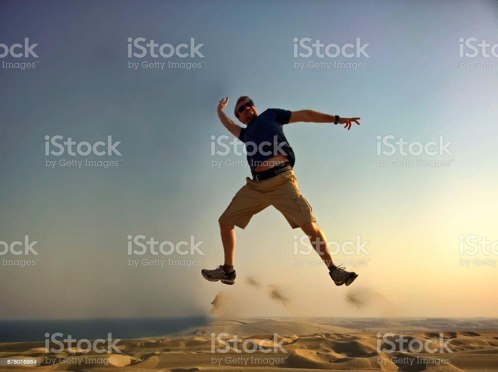 Männer mit an der Spitze der Dünen erhobenen Armen springen – Foto