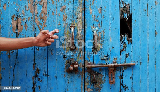 Young men knocking on old blue wooden door for opening.