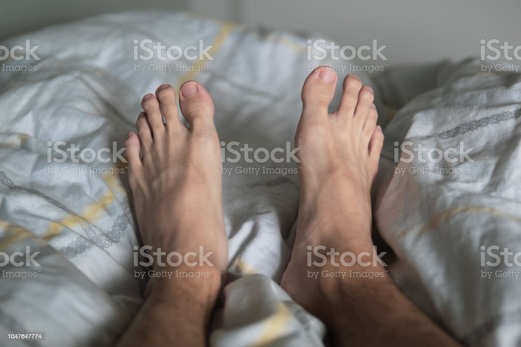 Men legs on the bed stock photo