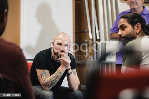Close up shot of a mid-adult hipster listening to someone speaking whilst sitting in a support group session.